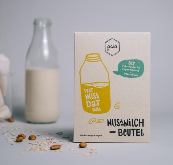 Verpackung eines Nussmilchbeutels neben einer Flasche Nussmilch