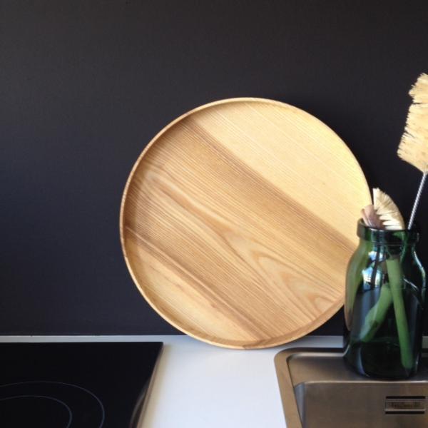 Rundes Tablett aus Holz vor schwarzer Wand