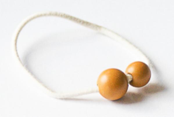 Weißes Haargummi mit ockerfarbenen Perlen