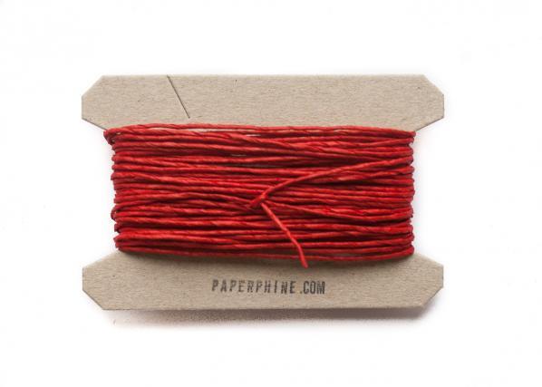 Rotes Geschenkband aufgewickelt auf einem Pappträger